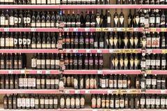 Bouteilles de vin rouge sur le support de supermarché Image stock