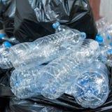 Bouteilles en plastique dans les sacs de déchets noirs attendant pour être pris pour réutiliser Photos libres de droits