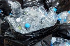 Bouteilles en plastique dans les sacs de déchets noirs attendant pour être pris pour réutiliser Photo stock