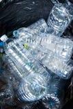 Bouteilles en plastique dans les sacs de déchets noirs attendant pour être pris pour réutiliser Photographie stock libre de droits