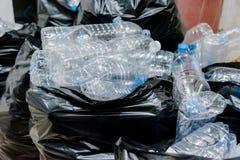 Bouteilles en plastique dans les sacs de déchets noirs attendant pour être pris pour réutiliser Images libres de droits