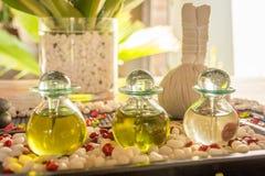 Bouteilles en verre avec le pétrole et les fleurs aromatiques sur la table en bois à la STATION THERMALE Photos stock