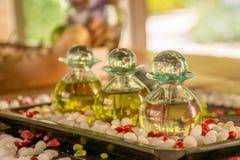Bouteilles en verre avec les parfums et les fleurs aromatiques sur la table en bois à la STATION THERMALE Photos stock
