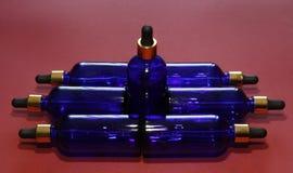 Bouteilles en verre bleues assorties avec un compte-gouttes d'or sur un fond rouge photographie stock libre de droits