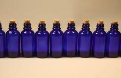 Bouteilles en verre bleues royales de compte-gouttes avec des lièges photo libre de droits