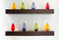 Bouteilles en verre colorées sur l'étagère en bois Photographie stock