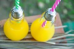 Bouteilles en verre d'ampoule avec le jus de fruit tropicaux orange frais sur le Tableau ouvert de café au coucher du soleil Fond photographie stock libre de droits