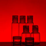 Bouteilles en verre dans la lumière rouge Photographie stock