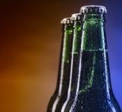 Bouteilles en verre de bière sur le fond brun et bleu Photographie stock libre de droits