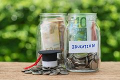 Bouteilles en verre de pot avec complètement de pièces de monnaie marquées comme éducation et le GR Photographie stock