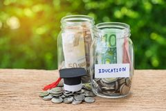 Bouteilles en verre de pot avec complètement de pièces de monnaie marquées comme éducation et le GR photos stock