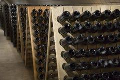 Bouteilles en verre de vin mousseux fermentant dans la cave d'établissement vinicole images stock