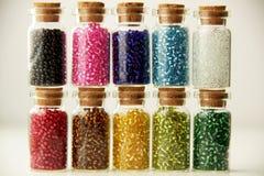 Bouteilles en verre minuscules remplies de perles Photographie stock libre de droits