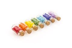 Bouteilles en verre minuscules remplies de perles colorées Images libres de droits