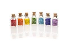 Bouteilles en verre minuscules remplies de perles colorées Image libre de droits
