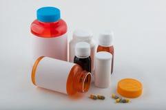 Bouteilles et pilules pharmaceutiques colorées sur le blanc Photographie stock libre de droits