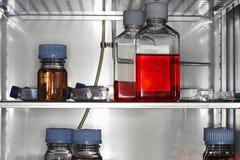 Bouteilles et récipients dans le réfrigérateur de laboratoire Photographie stock