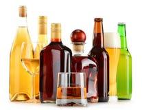 Bouteilles et verres de boissons alcoolisées assorties au-dessus de blanc Photographie stock