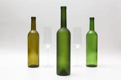 Bouteilles et verres de vin vides sur un fond blanc Images libres de droits