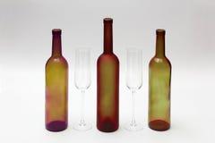 Bouteilles et verres de vin vides sur un fond blanc Photos stock