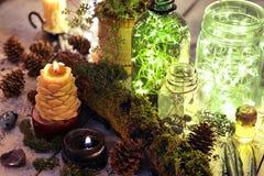 Bouteilles lumineuses avec les lumières et la bougie brûlante avec des éléments de nature et la mousse sur des planches photographie stock libre de droits