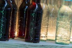 Bouteilles noires et blanches de boissons sur l'étagère en bois Images libres de droits