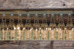 Bouteilles transparentes de boissons sur l'étagère en bois derrière le filet métallique Photos libres de droits