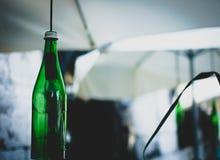 Bouteilles vertes sur les cordes sous des parapluies Image stock