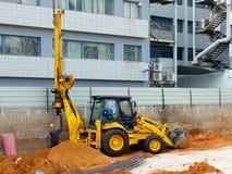 Bouteur avec l'installation ennuyée de pile au chantier de construction photo libre de droits