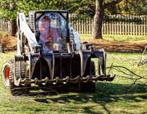 Bouteur transportant loin des débris d'arbre Image libre de droits