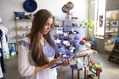 Boutique assistant using tablet with app icons in shop Stock Photos
