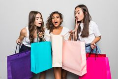 Black friday concept. Portrait of funky positive three mixed race having many colorful bags isolated on gray background stock photo