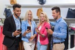 Boutique de mode des jeunes, amis de sourire heureux deux couples utilisant les clients futés d'achats de téléphone de cellules Photos stock