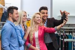 Boutique de mode des jeunes prenant des achats de photo de Selfie, amis de sourire heureux choisissant des vêtements Photographie stock libre de droits