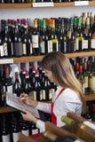Boutique de vin de Taking Inventory In de vendeuse Photographie stock libre de droits