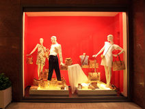 Boutique display window with mannequins in fashionable dresses. Fashion boutique display window with female mannequins in fashionable dresses with bags in the Royalty Free Stock Photo