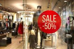 Boutique- och Sale tecken Shoppa fönsterskärm i stolpen om sal Royaltyfri Bild