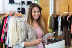 Boutique owner using a digital tablet Royalty Free Stock Photos