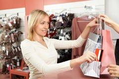 boutiquen betalar av kvinnan Royaltyfri Foto