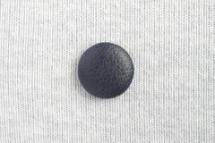 Bouton bleu sur le tissu blanc Image stock