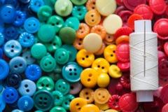Bouton coloré avec une aiguille et fil pour le fond Images stock
