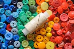 Bouton coloré avec une aiguille et fil pour le fond Image libre de droits