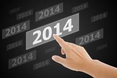 Bouton d'écran avec le nombre 2014 en main. Photographie stock