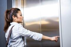 Bouton d'ascenseur de pressing de femme d'affaires image libre de droits