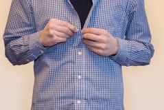 Bouton d'homme sur la chemise sur le fond blanc Photos stock