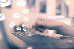 Bouton de clé de poussée de main de femme sur son ordinateur portable pour envoyer l'email images libres de droits