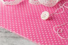 Bouton de ² d'anÐ d'aiguille goupillé sur le tissu de point de polka Photos stock