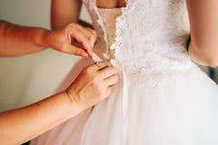 Bouton de maman vers le haut de la robe du ` s de jeune mariée Image libre de droits