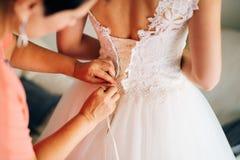 Bouton de maman vers le haut de la robe du ` s de jeune mariée Photographie stock libre de droits