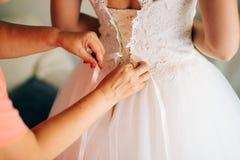 Bouton de maman vers le haut de la robe du ` s de jeune mariée Photographie stock